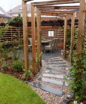 Garden re design in West London has Garden ideas such as cedar arches, path to patio and wall art/sculpture