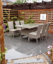 Garden redesigned with new patio in pretty area surrounded by plants and wall art and other Garden ideas