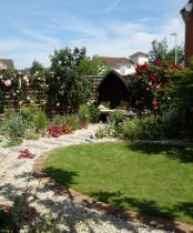 Small back garden with oval lawn and cottage garden plants by Rhoda Maw Garden Design
