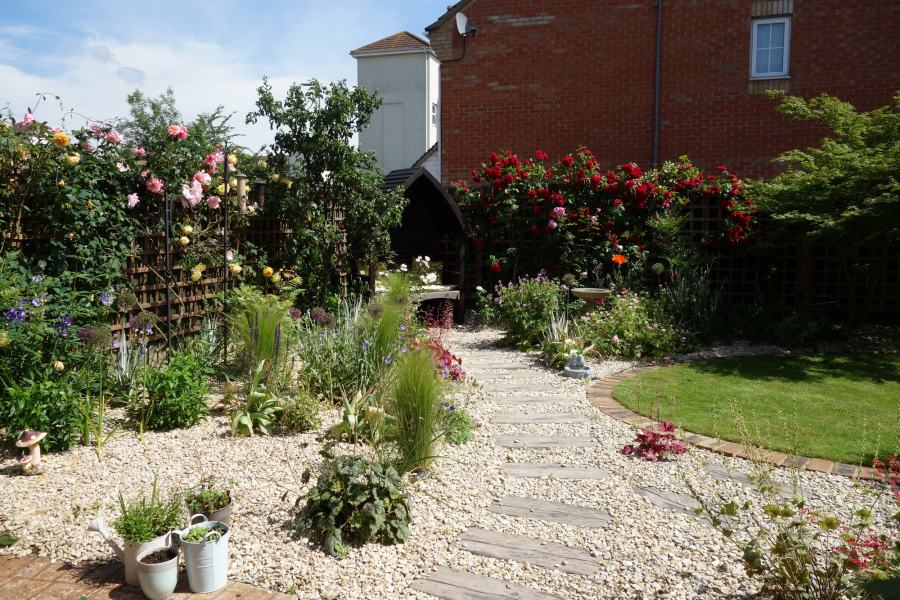 Small back garden in Uxbridge with stepping stones set in gravel leading to a Pergola seat and Cottage garden plants