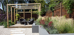 Contemporary back garden. With gravel, pergola, raised beds, modern furniture and planting